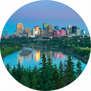 Picturesque scene of Edmonton, Canada, with green trees in front of crystal clear water and city buildings in the background.
