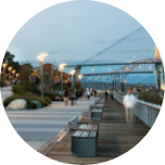 A promenade in New Westminster (Canada), with benches all the way along and a large steel bridge in the background.