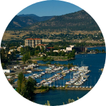 A harbour scene in Penticton (Canada), with boats in the harbour, green hills and mountains in the background.