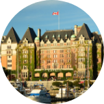 Grand building in Victoria, Canada, with greenery growing up the building and a Canadian flag flying on top.