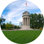 Temple-style tower in Waterloo, Canada, featuring a clock face and flag flying at the top.