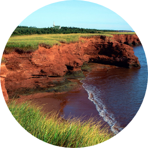 Red cliffs with a grassy area at the top and water crashing against the cliff in Prince Edward Island, Canada.
