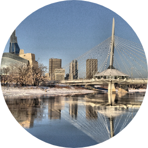 Bridge in Manitoba (Canada) with cityscape buildings all around and water in the forefront.