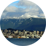 City in Canada at the foot of a mountain with water in front.