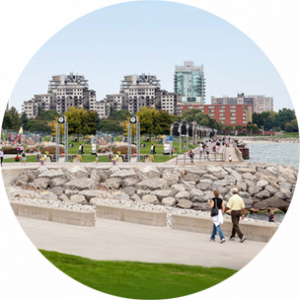 Paved walkway surrounding water in Burlington, with city buildings in the background.