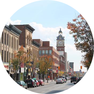 A main street running through Peterborough, Canada, with large buildings and a tall clock tower lining the street.