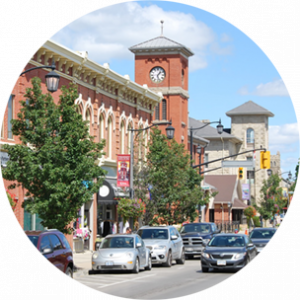 Main street with lots of cars, running parallel to a terracotta coloured building with a clock tower in Milton, Canada.