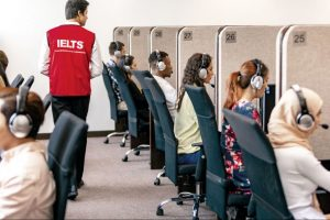 A group of test takers sat in booths with headphones on, sitting IELTS on computers.