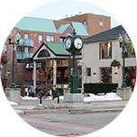 A lamppost clock and surrounding buildings in the town centre of Oakville, Canada.