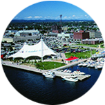 A harbour with white boats at the forefront, and lots of buildings behind it in Sault Ste Marie, Canada.