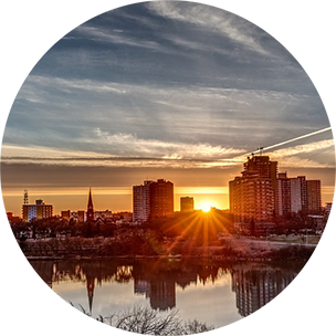 Sun setting over city buildings in Ajax, Canada, with water in the forefront.